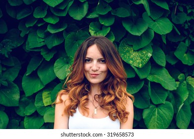 Portrait of nice young woman, against background of summer green park, green leaves.beautiful woman with curly hair