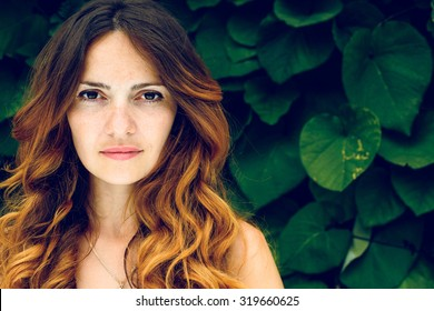 Portrait of nice young woman, against background of summer green park, green leaves.beautiful woman with curly hair. sad beautiful woman