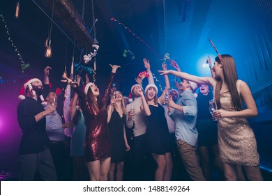 Portrait of nice-looking attractive smart cheerful cheery positive glad ladies and guys having fun dream celebratory flying decorative elements at luxury fogged lights nightclub indoors