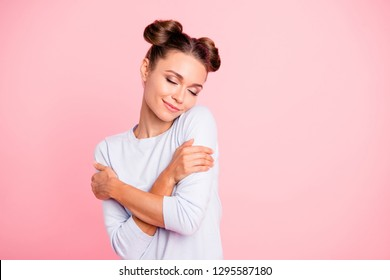 Portrait of nice-looking sweet lovable attractive winsome fascinating well-groomed lovely calm peaceful cheery girl hugging herself isolated over pink pastel background