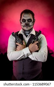 Portrait of a nicely dressed man with skull makeup. Horror and Halloween themed, shot with theatrical lighting and effects. Colored Fog behind the model