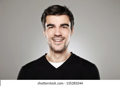 Portrait of a normal boy smiling over grey background / Attractive young man in studio looking at camera