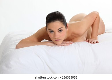 Portrait of a nude woman lying on a bed