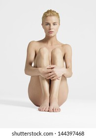 Portrait of a nude young woman sitting with hands on knees against white background