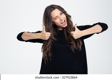 Portrait o a cheerful woman winking and showing thumbs up isolated on a white background