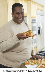 Portrait of an obese African American man holding slice of pepperoni pizza while standing by kitchen counter