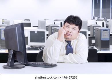 Portrait of obese businessman working with computer while sitting in the office