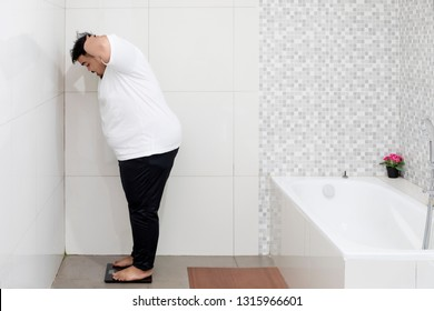 Portrait of an obese man looks shocked while standing on the scale. Shot in the bathroom