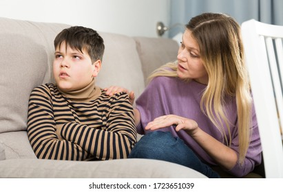 Portrait of offended boy and angry mother having quarrel at home