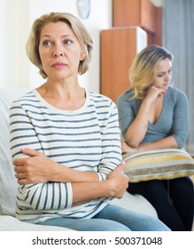 Portrait of offended mature woman and displeased young girl quarrelling