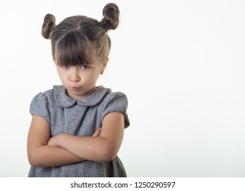 Portrait of offended and moody cute european kid with brunette hair frowning and pursing lips, looking from under forehead bothered and upset feeling insulted, holding hands crossed on chest