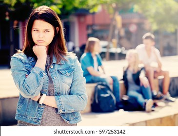 Portrait of offended outcasted teenager girl being mobbed by other teenagers outdoors