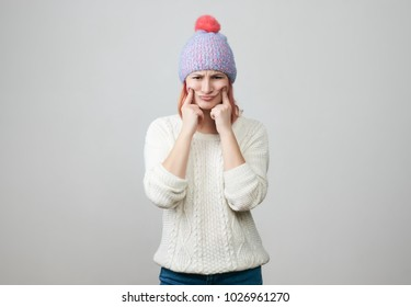Portrait of offended unhappy beautiful woman in knitted hat, keeps hands crossed, curves lips, displeased with everything, feels frustrated and upset. Negative emotions and feelings