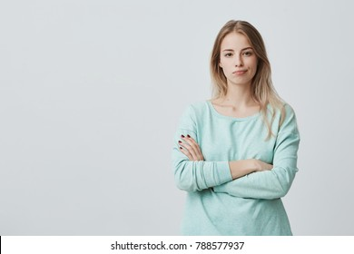 Portrait of offended unhappy beautiful woman with long blonde hair keeps hands crossed, curves lips, displeased with everything, feels frustrated and upset. Negative emotions and feelings