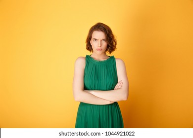 Portrait of offended woman with arms crossed looking at camera isolated on orange