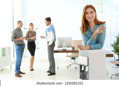 Portrait of office employee with glass near water cooler at workplace. Space for text