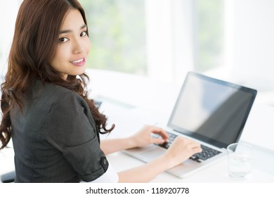 Portrait of an office girl computing on laptop