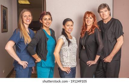 Portrait of office staff standing in office area.