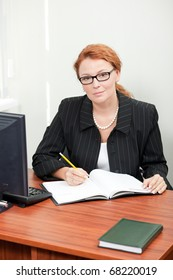 Portrait of office worker lady sitting at her table in office. Happy red-haired lady in glasses working in office and looking at camera while writing something in her notebook.