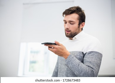 A portrait of an office worker talking to someone using the spea