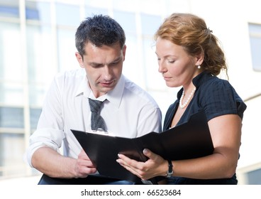 Portrait of office workers signing documents outdoors. Red-haired lady and her boss looking at documents from foreign partners in front of office building.
