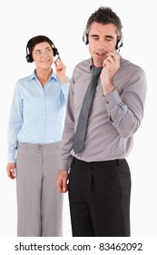 Portrait of office workers speaking through headsets against a white background
