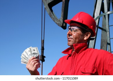 Portrait of oil worker with dirty face and US dollar bills in his hands on pump jack oil rig.