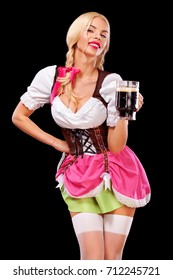 Portrait of Oktoberfest girl - waitress, wearing a traditional Bavarian dress, serving big beer mugs on black background.