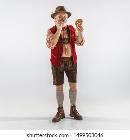 Portrait of Oktoberfest senior man in hat, wearing the traditional Bavarian clothes. Male full-length shot at studio on white background. The celebration, holidays, festival concept. Eating puff.