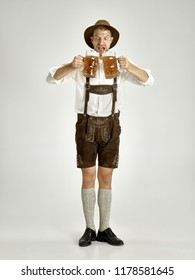 Portrait of Oktoberfest young man in hat, wearing a traditional Bavarian clothes standing with beer at full-length at studio. The celebration, oktoberfest, festival concept