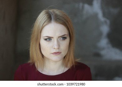 Portrait of Oktyabrina with her anxious facial expression and gaze on the gray wall background