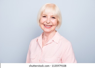 Portrait of old adult blonde glad cheerful lady smiling, over grey background, isolated