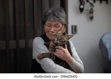 Portrait of an old Asian lady holding a brown patch cat in Japan.