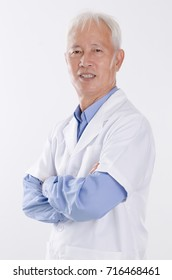 Portrait of old Asian man in lab coat smiling, standing isolated on white background.