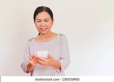 Portrait of old Asian woman looking at screen of smartphone and smile. People and technology concept. White background.