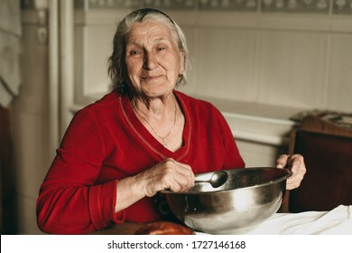Portrait of an old beautiful gray-haired retired woman preparing to eat, kneading dough at home in quarantine. Happy grandmother lives in old age. Homemade food.