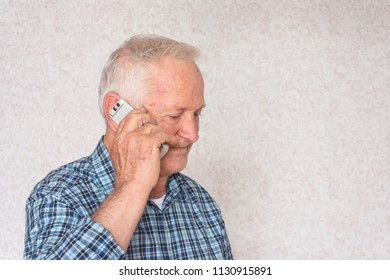 Portrait of a old business man holds a mobile phone and talking about business.