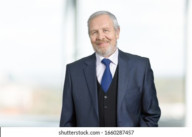 Portrait of old businessman. Senior 70 years old man in business suit. Bright blurred background.