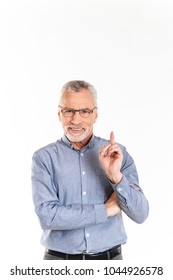 Portrait of old cheerful man in glasses pointing up with finger and looking camera isolated over white