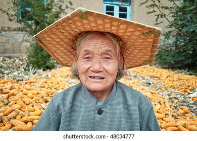 Portrait of a old Chinese women.She is working in yard of her house.