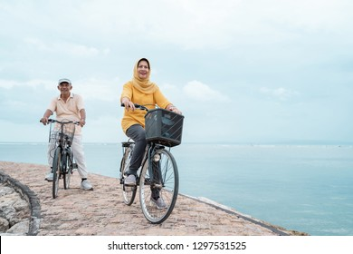 portrait of old couple ride bicycle and workout together outdoor