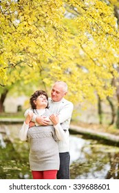 portrait of a old couple standing in autumn park