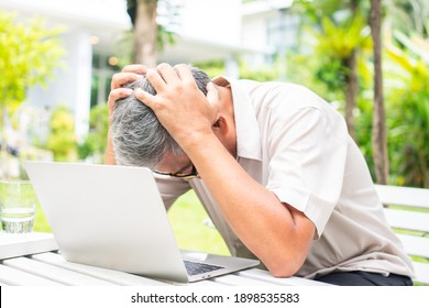 Portrait of an old elderly Asian man holds the head with his hand cause of stress after try to use a computer laptop in the backyard after retired. Concept of Ageism and Hobbies after retirement.