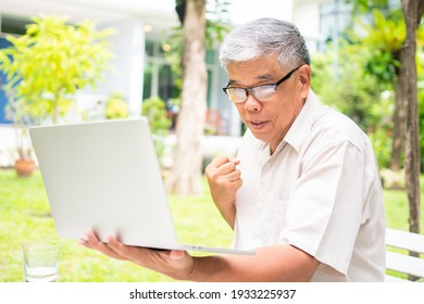 Portrait of an old elderly Asian man is holding a computer laptop and surprised after got some email and read some news in the backyard. Concept of no Ageism and Hobbies after retirement.