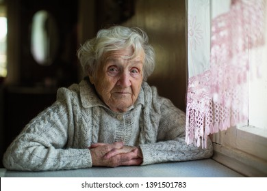 Portrait of an old elderly woman. Pensioner in his house.