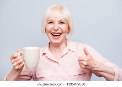 Portrait of old excited lady showing thumbs up gesture, smiling laughing, holding cup drinking coffee, tea, beverage on grey background, isolated