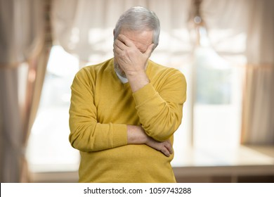 Portrait of old grandpa doing facepalm. Forgetful old man holding his hand to his forehead.
