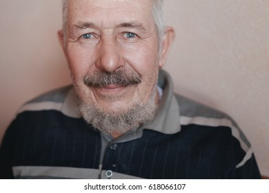 Portrait of old gray-haired smiling man with a beard and mustache.