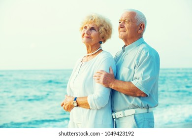 portrait of old happy pensioners standing together on the beach