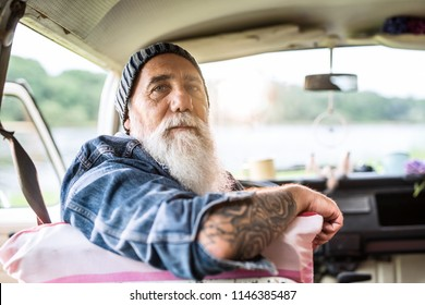 Portrait of an old hipster sitting in a van looking at camera. he is tattooed and he wears a white beard and a cap
